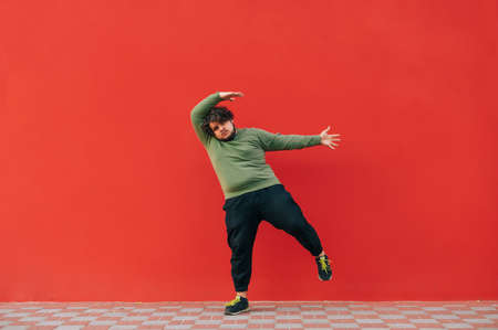 Funny young man with overweight and curly hair dances against the background of a red wall, looks at the camera and moves. 免版税图像
