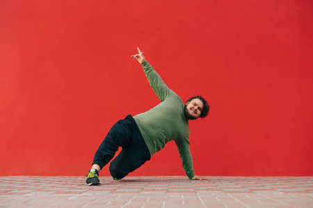 Positive overweight young man shows a dance performance on the street against the backdrop of a red wall, looks at the camera and smiles.