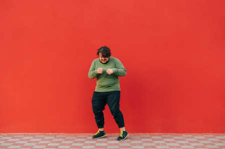 Funny fat man in a green sweatshirt dancing on the street on a background of a red wall. Overweight man dancing on red background. 免版税图像