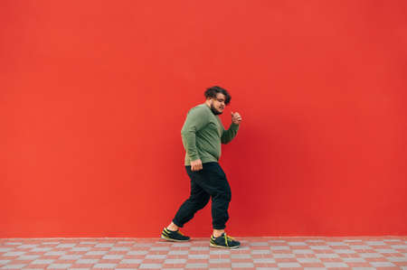 Stylish overweight young man in casual clothes listens to music in wireless headphones and dances on a red wall background, side view.
