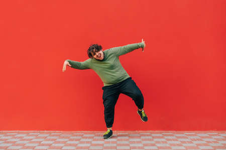 Happy overweight young man in casual clothes dancing on red background and looking at camera with smiling face. Isolated.
