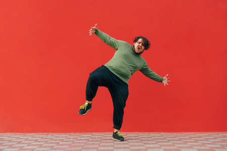 Ð¡harismatic fat man in headphones shows a dance performance on the street against the backdrop of a red wall. Fat guy with curly hair dances on a red background. 免版税图像