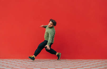 Fat dancer shows hip hop performance on red wall background. Overweight man dancing breakdance on red background