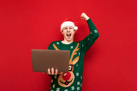 Joyful young man in Christmas clothes stands with a laptop in his hand and is emotionally pleased to win on a red background, looks into the camera with his arm raised up and shouts with happiness.