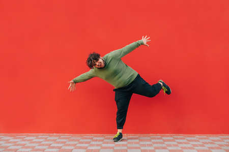 Full-length portrait of a funny fat man dancing on a red background, wearing casual clothes, looking at the camera and smiling.