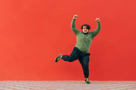 Funny fat guy dancing on a red wall and listening to music on headphones. Cheerful overweight man and casual clothes shows a dance performance.