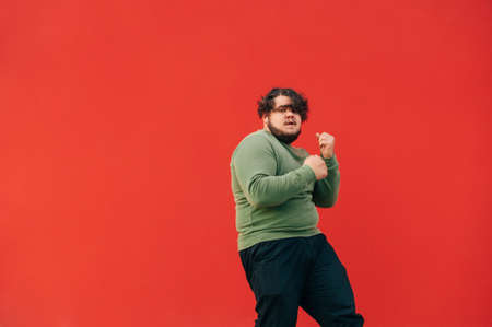 Fat man in a green sweatshirt and headphones dances on a red background and looks at the camera. Overweight guy shows a dance performance, isolated.