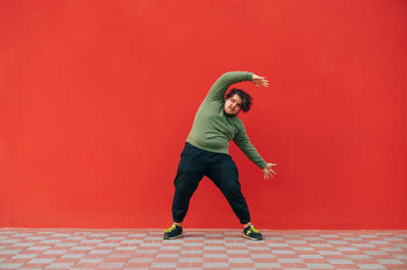 Funny fat man in casual clothes trains on a red wall, looks at the camera and makes hand movements. Overweight man dancing on red background. 免版税图像