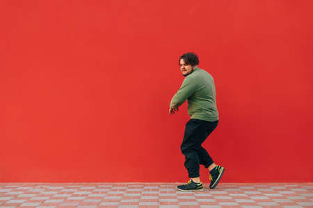 Funny fat man in green sweatshirt dances hip hop dancing on red wall background and listens to music on headphones.