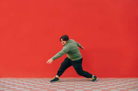 Fat charismatic man dancing breakdance on a red wall background, wearing casual clothes. Overweight guy in casual clothes dancing hip hop outdoors on red background 免版税图像