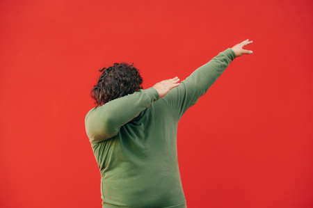 Funny fat man in casual clothes dancing dub dance on red wall background. Isolated. Close up 免版税图像