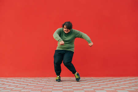 Funny fat man in casual clothes shows hip hop performance on the street against the backdrop of a red wall with a smile on his face, listens to music on headphones and smiles. 免版税图像