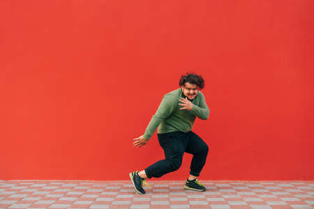 Active overweight young man dances hip hop on a background of a red wall, looks at the camera and smiles, wears casual clothes. 免版税图像