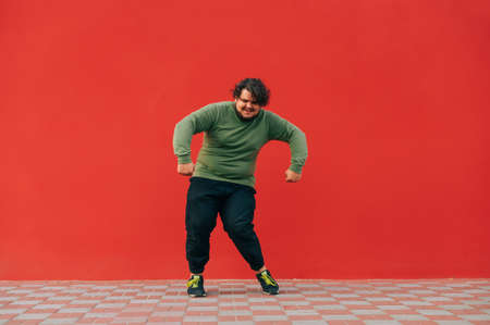 Charismatic positive fat man in casual clothes dancing on a red wall background. An overweight guy shows a dance performance on the street.