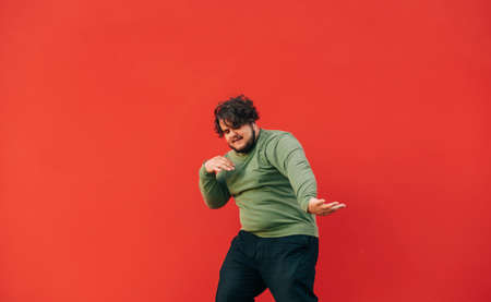Fat young man showing hip hop performance on red background. Overweight guy dancing on a red wall background. 免版税图像