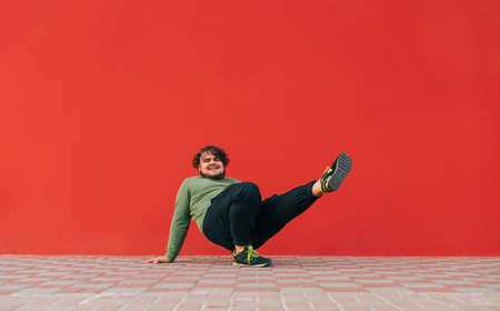 Positive overweight young man dancing hip hop on the street on a red wall background. Tostun shows a dance ball performance on a red background. 免版税图像