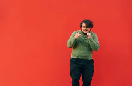 Positive overweight man and green sweatshirt funny dancing on red wall background and smiling. Fat man shows a dance performance. Isolated.