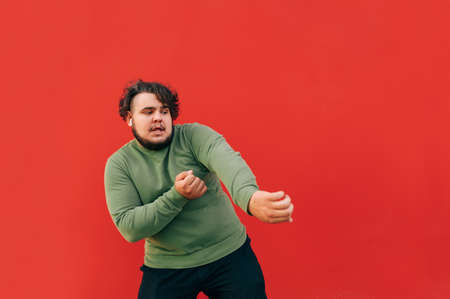 Charismatic overweight man with curly hair dancing on red background and looking away at copy space isolated on red background. 免版税图像