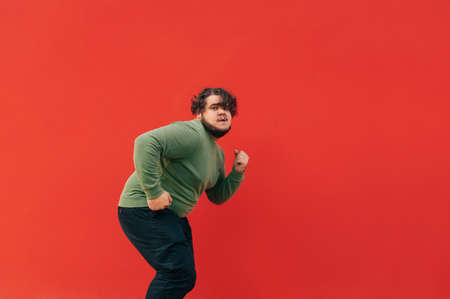 Stylish overweight young man dances on a red wall and listens to music in wireless headphones, looking at the camera with a serious face.