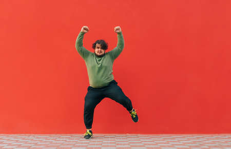 Positive fat dancer in casual clothes shows a performance on the street on a red background. Funny fat man dancing against the red wall.