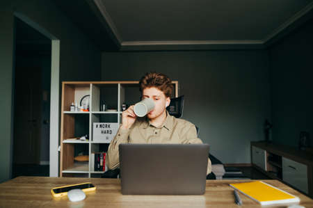 Young male worker in shirt working at home remotely on laptop and drinking hot beverage from cup. Freelancer in wireless headphones works at home in the bedroom and drinks tea. Remote work.