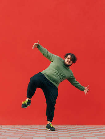 Vertical photo of a funny fat man standing on one leg against a red wall and dancing, looking at the camera.