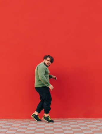 Vertical photo of dancing fat man in stylish street clothes dancing on red wall background and looking at camera.