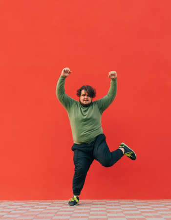 Full-length portrait of a fat dancer shows a performance against a red wall, looks at the camera and listens to music on headphones. Isolated. Vertical. 免版税图像