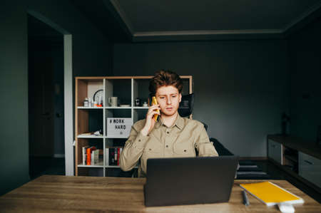 Serious young man in a shirt uses a laptop at home at work and talks on the phone. Concentrated freelancer works at home on remote work. Quarantine.