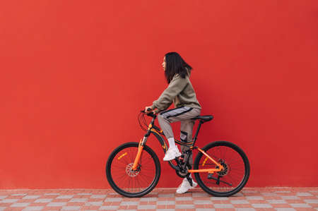 Beautiful woman rides a bicycle on a background of a red wall, looking ahead at the copy space. Hispanic woman standing on a bicycle on a red background. Banco de Imagens