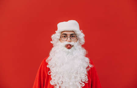 Funny Santa stands on a red background, looks at the camera and shows his tongue. Funny santa claus with beard makes funny face isolated on red