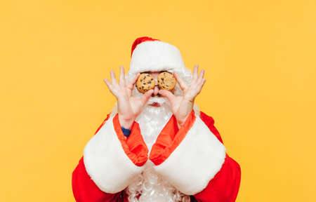 Funny santa with chocolate chip cookies in hands holding eyes near yellow background. Santa Claus and Christmas cookies, isolated. New Year