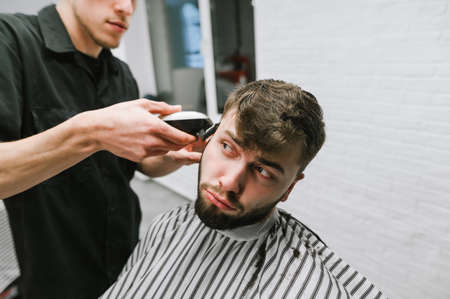 A funny young man with a beard cuts a hairdresser with a disgruntled face, looks away. Barber trims hair clipper dissatisfied client. Haircut in male hairdresser concept.