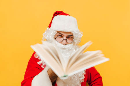 Closeup portrait of Santa Claus in the studio in front of the yellow wall holding a book and showing it to the viewers. Santa is offering viewers to read a book.