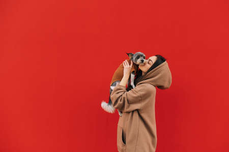 Cute woman hugs and kisses a dog in her arms on a red wall background. lady took the pet in her arms and kissed it. Isolated. Copy space