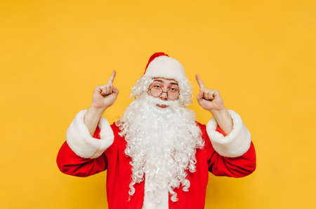 Cheerful and positive Santa Claus is pointing up on a copy space. Santa on a yellow background is raising his hands up, advertising and bringing attention to a blank space.