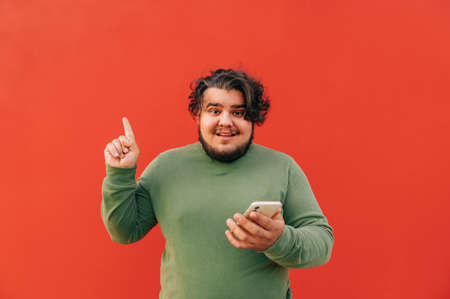 Young attractive overweight hispanic man is having an idea, and expressing it with a gesture, pointing his finger up, while using a smartphone. Reklamní fotografie