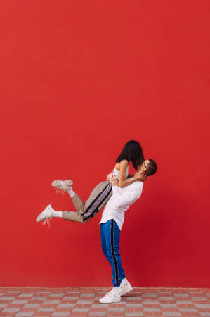 Passionate couple of stylish young man and woman in street clothes stand on a background of a red wall, a man holds a woman in his arms and passionately kisses. Valentine's Day. February 14th Reklamní fotografie