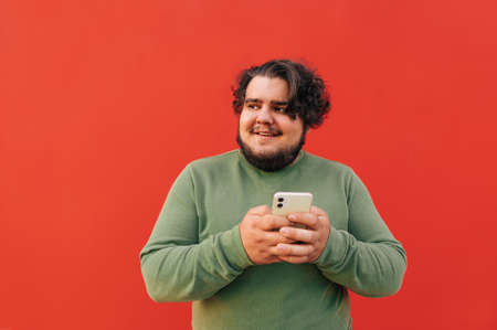 Young corpulent bearded hispanic guy is looking aside, holding and using his smartphone, feeling cheerful, standing on a red background. Reklamní fotografie