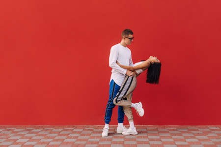 Stylish couple in love standing on the street on a background of red walls in fashionable casual clothes man hugging a girl by the waist. Valentines day. Reklamní fotografie