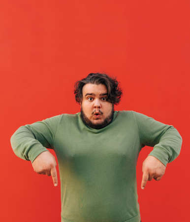 Vertical shot of a funny obese hispanic guy with a stylish haircut pointing his fingers down, advertising a product, being emotional, standing on a red background. Reklamní fotografie