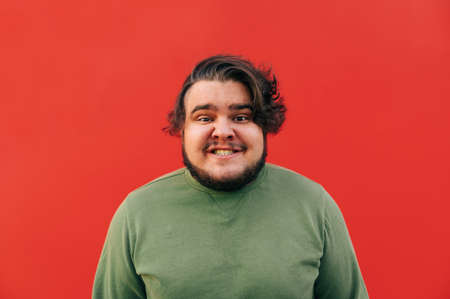 Hilarious corpulent young hispanic man is smiling with a toothy smile, being funny, silly and crazy, standing in front of the red wall. Reklamní fotografie
