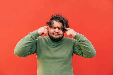 Angry bearded fat hispanic young man is expressing a thinking gesture by touching his head with his fingers, looking annoyed, frowning, standing on a red background.