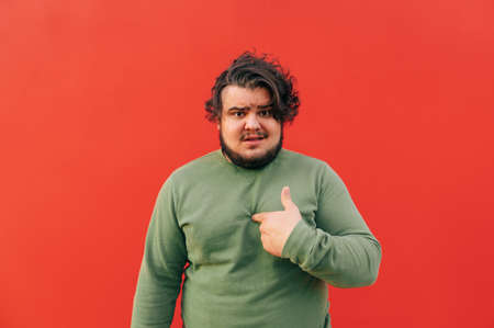 Offended hispanic man is pointing his finger at himself expressing a conflict and misunderstanding, feeling angry and frustrated, standing on a red background.