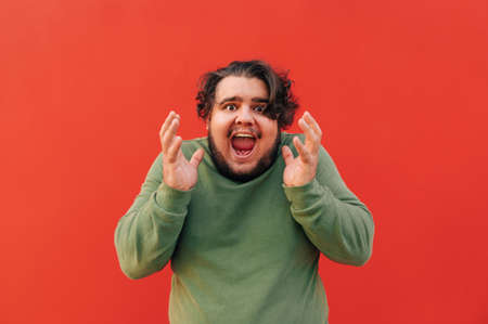 Frustrated young obese bearded guy is shouting and raising his hands up, being angry and emotional, standing in front of a red wall. Reklamní fotografie