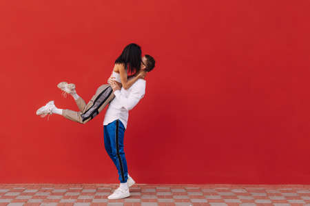 Loving young couple stands on Valentine's Day against the backdrop of a red wall and having fun, a strong man lifted a woman in his arms and passionately kisses. February 14th.