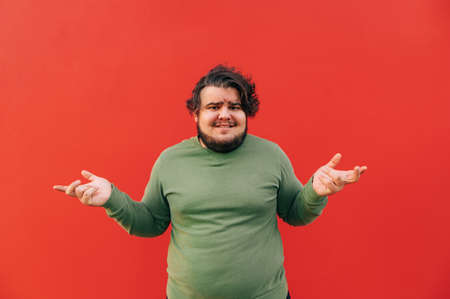 Baffled young hispanic bearded overweight man is expressing a confusion by throwing up his hands, frowning, feeling puzzled and unsure. Red background.