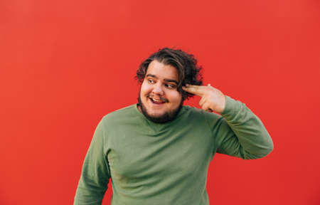 Crazy hilarious young hispanic guy is showing a shooting gesture, joking and smiling, being funny and covertly frustrated, trying to overcome stress.