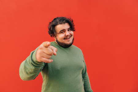Attractive young hispanic guy with a stylish haircut is pointing his finger at the camera and the viewer, being friendly and positive. Reklamní fotografie