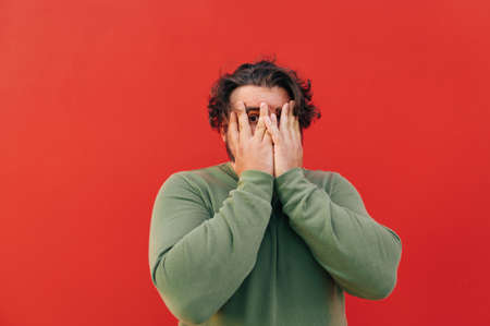 Funny corpulent young man with a curly hair is hiding his face with his hands, feeling scared, peeping at the camera through his hands.